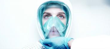 A futuristic mask is placed on a woman by a medic in a white environment